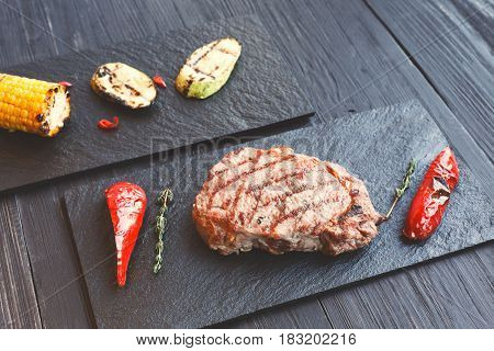 Grilled beef steak cooked on barbecue on dark wooden table background. Fresh juicy roasted red meat on black stone board. Restaurant food, delicious dish