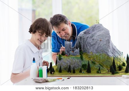 Father and son work on model building school project. Kids and parent build miniature scale model mountain for geography class. Extracurricular activities and family hobby. Art and crafts for child.