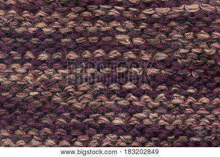 Abstract knitted purple background texture. Textile pattern of purple woolen handmade cloth. Macro of back loop wool winter fabric with geometric color ornament