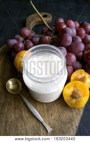 Breakfast, Yogurt, Plums, Grapes On A Wooden Board