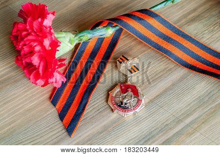 VELIKY NOVGOROD,RUSSIA-CIRCA APRIL,2017. 9 May card - closeup of medal of Great patriotic war with red carnation and George ribbon lying on the wooden table. 9 may background