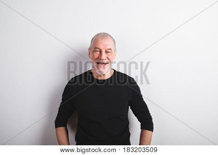 Face of handsome senior man in black sweater smiling. Studio shot against white wall.