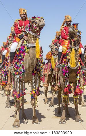 JAISALMER INDIA - FEBRUARY 09 2017 : Camel and indian men wearing traditional Rajasthani dress participate in Mr. Desert contest as part of Desert Festival in Jaisalmer Rajasthan India