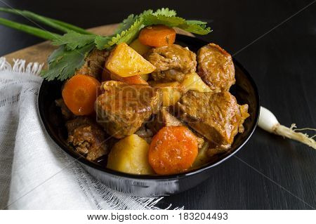 Beef Stew With Potatoes, Carrots And Herbs On Black Background With Copy Space, Top View