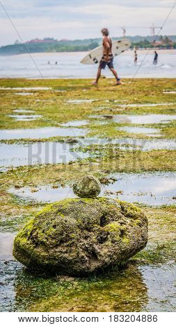Zen-like Stones Covered with Moos on Beach during Low Tide, Nice Water Reflection, Lonely defocused surfer walk on the background, Nusa Dua, Bali, Indonesia.