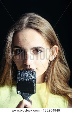 pretty woman painter or cute sexy girl builder with paintbrush tassel or brush building tool painting with black color has dirty face long hair in yellow vest. repair construction concept