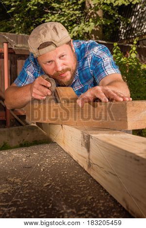 Carpenter chipping the wooden plank by the  plane
