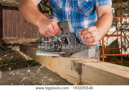 Carpenter chipping the wooden plank by the electric plane