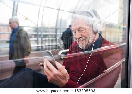 Handsome senior man holding smart phone, headphones on his ears, listening music, sitting in glass passage. View through glass.