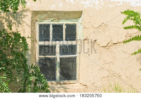Window of an old Ukranian abandoned clay-walled hut.