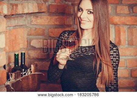 Elegant beauty lady long hair full make up wearing black dress tasting wine in rural cottage interior celler