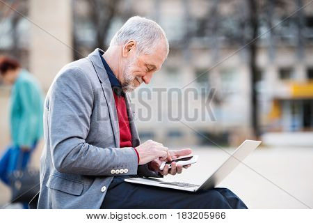 Handsome senior man in town sitting on bench, holding laptop and smart phone, making phone call. Sunny spring day.