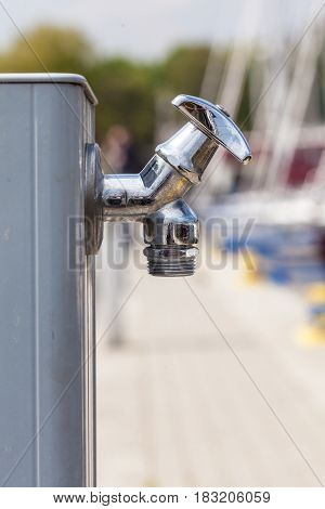 Hydration during walking concept. Small metal tap water outside for use by pedestrians.