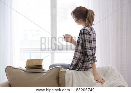 Beautiful young woman with cup of tea and books resting at home