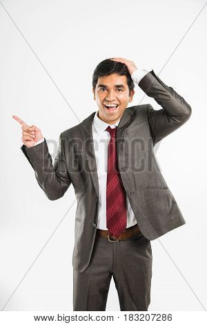 Indian young Businessman pointing copy space. Happy young man in brown suit looking at camera and smiling while standing against white background and pointing copy space