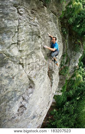male rock climber. rock climber climbs on a rocky wall. man makes hard move