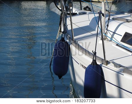 Left side of white sailing boat with two blue fenders