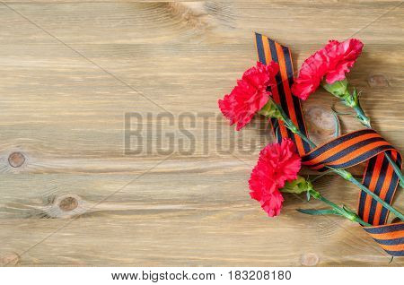 9 May background - red carnations and George ribbon lying on the wooden background free space for text for 9 May celebration. 9 May postcard