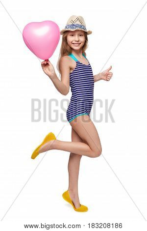 Full length child girl in swimsuit and summer hat with pink balloon heart shape gesturing thumb up, studio portrait