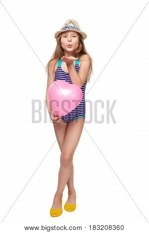 Full length child girl in swimsuit and summer hat with pink balloon heart shape blowing a kiss, studio portrait