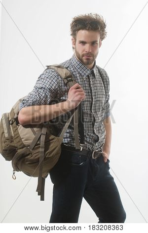 Traveling travelling and vacation. Handsome man or traveler with beard and stylish hair haircut with backpack bag in checkered shirt jeans with suspenders on white background.