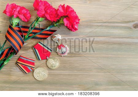 VELIKY NOVGOROD,RUSSIA-CIRCA APRIL,2017. 9 May Victory day still life with medals of Great patriotic war red carnations and George ribbon lying on the wooden background. 9 May card