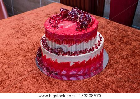 Two tier white and red cake with pomegranate
