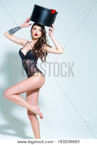 pretty woman or cute sexy girl in erotic black bodysuit with long curly brunette hair has red lips on adorable face and tattoo on hand holds big present box on grey background