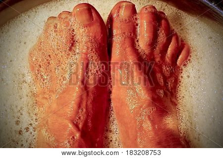 Close up of Feet in soapy water during pedicure