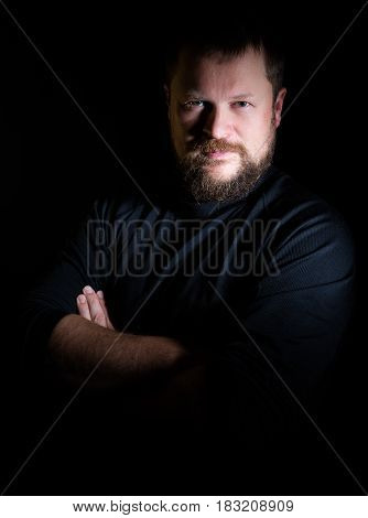 Solid bearded middle-aged man portrait on black background