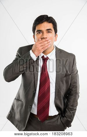 indian young businessman in keep silence pose while covering mouth, standing isolated over white background