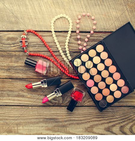 Women's accessories: necklace, nail polish, lipstick, hair clip, eye shadow. Top view. Toned image.