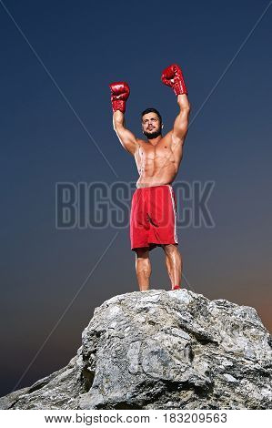 Boxing champion celebration victory standing on a rock with his arms raised in the air shirtless muscular strong competitive first championship fighter sportsman athlete competition winner winning.