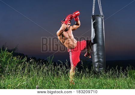 Professional male fighter working out outdoors kicking a punching bag with his knee copyspace kickboxing Muay Thai martial arts combat kick fighting training sports fitness muscles ripped body torso .