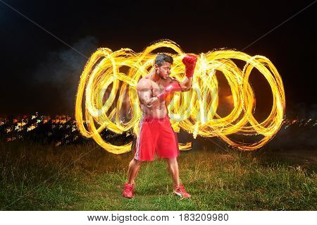 Horizontal full length shot of a powerful forceful young male boxer posing in a fighting stance outdoors fire and flames on the background copyspace power strength sports motivation athlete lifestyle .