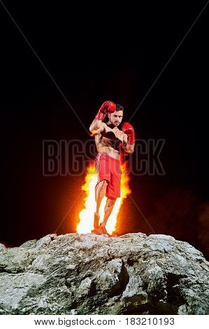 Full length vertical shot of a strong young muscular male fighter in a fighting stance wearing boxing gloves standing on top of a rock with fire flaming behind his back winning confidence power force.
