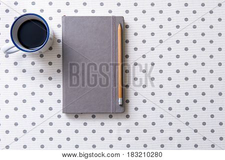 Sharp pencil is on covered gray diary nearby small mug with dark coffee. Top view. Copy space