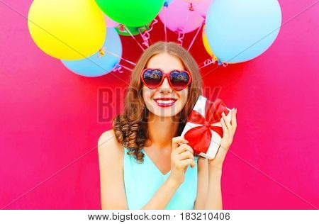 Portrait Happy Smiling Woman In Hands A Gift Box Over An Air Colorful Balloons Pink Background