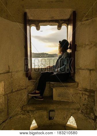 Woman looking through a Window and admiring a landscape