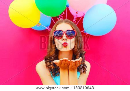 Portrait Woman Sends An Air Kiss Holds An Air Colorful Balloons On A Pink Background