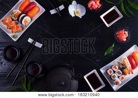 Japanese sushi dish frame on black wooden background with copy space
