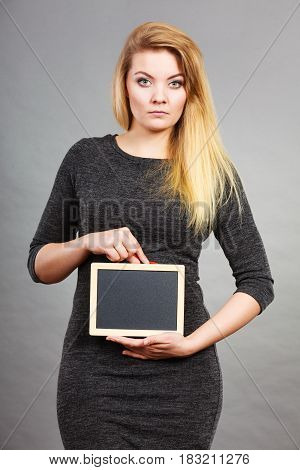 Tummy belly problems pain digestion constipation concept. Woman holding blank black board on stomach