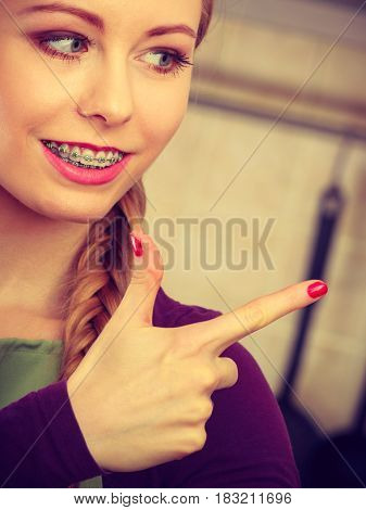Happy smiling young woman with braces on her teeth pointing at something with finger