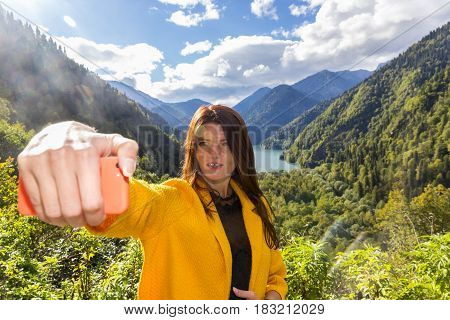 Young beautiful woman making emotional selfi on picturesque landscape background