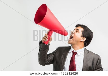 indian male businessman announcing or spreading news using red speaker or mega mic made up of paper, isolated over white background