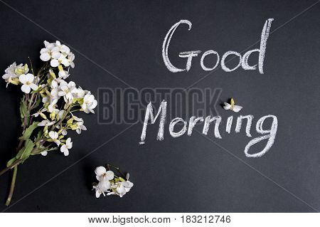 Text Good morning white flowers on a black background.