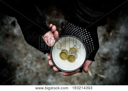 Dirty hand of a person grips a metal Cup In a mug find the coins.
