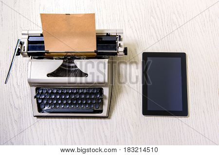 Technology development. Vintage typewriter is beside modern tablet at wooden table. Top view
