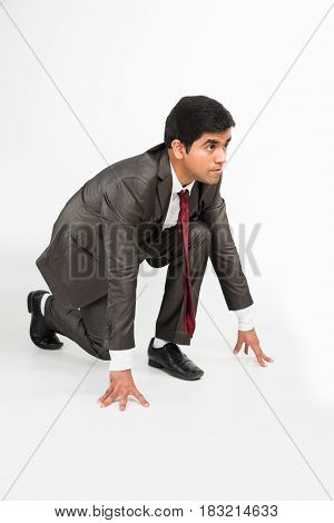 Young indian smart and determined businessman standing in start position, isolated over white