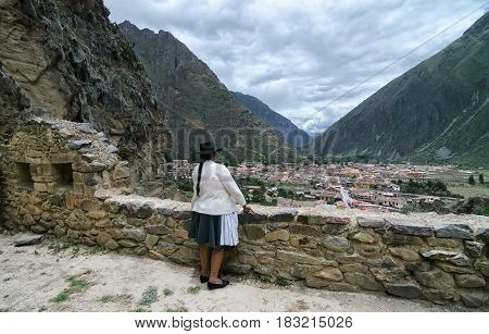 OLLANTAYTAMBO PERU 10 FEBRUARY back view of anonymous Peruvian woman in traditional clothes looking from Inca ruin wall to the city and mountains